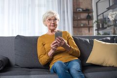 Geïmponeerde oude dame die op laag bij woonkamer met telefoon rusten stock fotografie
