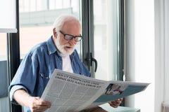 Geïmponeerde oude mens die van publicatie thuis genieten stock fotografie