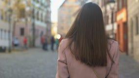 Geïnspireerde aantrekkelijke jonge dame die gang hebben rond mooie stad op zonnige dag stock videobeelden