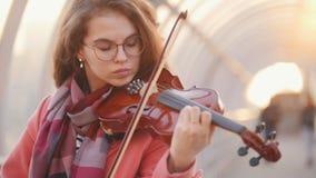 Geïnspireerde jonge vrouw het spelen viool solo op de straat stock video