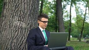 Geïnspireerde jonge zakenman die aan gras in park werken, die bureau aan routine ontsnappen stock footage