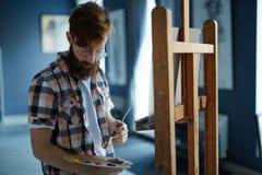 Geïnspireerde Kunstenaar Painting Picture in Studio royalty-vrije stock fotografie