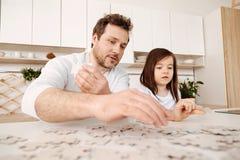 Geïnspireerde vader en dochter die een puzzel samen doen royalty-vrije stock fotografie