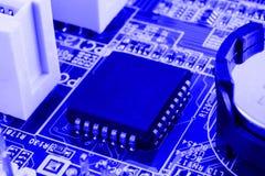 Geïntegreerde halfgeleidermicrochip op blauwe kringsraad representatief voor de high-tech de industrie en computerwetenschap Stock Afbeelding