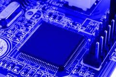 Geïntegreerde halfgeleidermicrochip op blauwe kringsraad representatief voor de high-tech de industrie en computerwetenschap Stock Fotografie