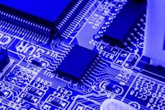 Geïntegreerde halfgeleidermicrochip op blauwe kringsraad representatief voor de high-tech de industrie en computerwetenschap Stock Foto