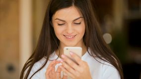 Geïntrigeerde meisjesglimlachen zoals texting stock video