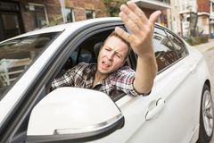 Geïrriteerde jonge mens die een auto drijven Geïrriteerde bestuurder Stock Fotografie