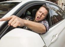 Geïrriteerde jonge mens die een auto drijven Geïrriteerde bestuurder Royalty-vrije Stock Foto's