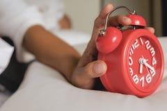 Geïrriteerde jonge vrouw die haar wekker in de ochtend uitstellen royalty-vrije stock afbeeldingen