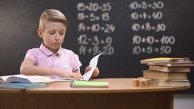 Geïrriteerde schooljongen tearing pagina van notitieboekje, onbekwaam om moeilijke taak op te lossen stock footage