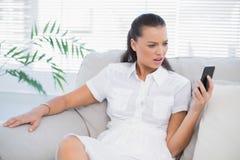 Geïrriteerde vrouw die in witte kleding haar smartphone bekijken Stock Foto