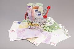 Geïsoleerd boodschappenwagentjehoogtepunt van euro bankbiljetten Stock Afbeelding