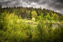 Geïsoleerd droomhuis naast het meer, in dramatische stormachtige hemel en wilde aard, cerknica Slovenië royalty-vrije stock afbeelding
