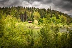 Geïsoleerd droomhuis naast het meer, in dramatische stormachtige hemel en wilde aard, cerknica Slovenië royalty-vrije stock afbeeldingen
