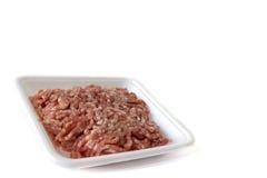 Geïsoleerd fijngehakt rood varkensvlees op de witte achtergrond van het plastic containerpakket Stock Afbeeldingen