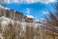 Geïsoleerd huis in de sneeuw in wintertijd, Italië stock foto