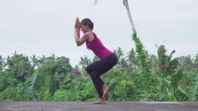 Geïsoleerd op wit Garudasana stelt De jonge yoga van vrouwenpraktijken stock videobeelden