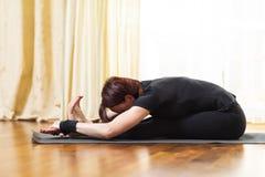 Geïsoleerd op wit Kaukasische Vrouw het Praktizeren Yogaoefening binnen bij Heldere Middag Het zitten in Pashchimottasana stelt stock fotografie