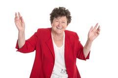 Geïsoleerd portret: gelukkig en toejuichend oudere dame in rood jasje Stock Foto's