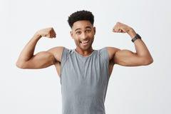 Geïsoleerd portret van de jonge vrolijke aantrekkelijke atletische donker-gevilde mens met afrokapsel in sportief grijs overhemd royalty-vrije stock fotografie