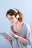 Geïsoleerd portret van een mooie jonge vrouw die met tabletcomputer spelen Stock Fotografie