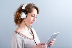 Geïsoleerd portret van een mooie jonge vrouw die met tabletcomputer spelen Royalty-vrije Stock Afbeeldingen