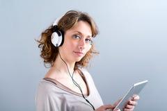 Geïsoleerd portret van een mooie jonge vrouw die met tabletcomputer spelen Stock Foto's
