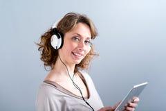 Geïsoleerd portret van een mooie jonge vrouw die met tabletcomputer spelen Royalty-vrije Stock Afbeelding
