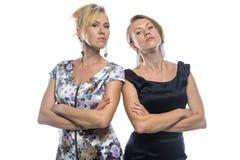 Geïsoleerd portret van twee ernstige zusters Stock Foto