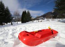 Geïsoleerd rood loodje om in de sneeuw te spelen royalty-vrije stock fotografie