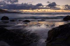 Geïsoleerd strand onder een dramatische zonsonderganghemel Royalty-vrije Stock Foto