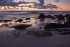 Geïsoleerd strand onder een dramatische zonsonderganghemel Royalty-vrije Stock Afbeeldingen