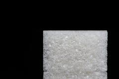 Geïsoleerd stuk van suiker op een zwarte achtergrond Stock Fotografie
