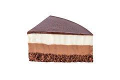 Geïsoleerde die chocoladecake van drie verschillende lagen, het wit, de melk en dark van de chocolademousse met chocolade wordt g Royalty-vrije Stock Foto's
