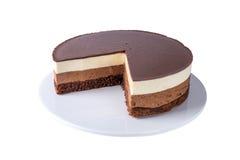 Geïsoleerde die chocoladecake van drie verschillende lagen, het wit, de melk en dark van de chocolademousse met chocolade wordt g Stock Fotografie