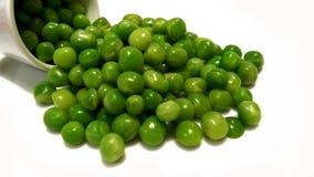 Geïsoleerde gezonde verse groene die erwten op witte achtergrond worden verspreid Stock Foto's