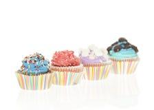 Geïsoleerde groep van Vier Kleurrijke Cupcakes Stock Foto