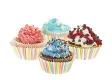 Geïsoleerde groep van Vier Kleurrijke Cupcakes Stock Foto's