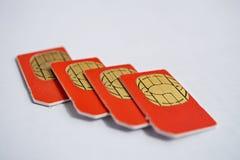 Geïsoleerde groep van vier rode die SIM-kaarten in de mobiele telefoons (celtelefoon) worden gebruikt met nadruk op gouden micro- Stock Afbeelding