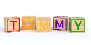 Geïsoleerde houten stuk speelgoed kubussen met brieven met naam Tommy Stock Foto's