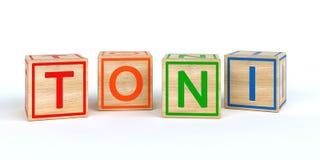 Geïsoleerde houten stuk speelgoed kubussen met brieven met naam Toni Stock Fotografie