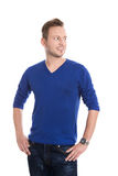 Geïsoleerde jonge blonde mens die in blauwe trui zijdelings aan te kijken Royalty-vrije Stock Afbeeldingen
