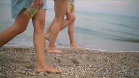 Geïsoleerde mening van drie paren die slanke vrouwelijke benen met glasflessen van drank in handen op het strand door stappen stock videobeelden