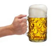 Geïsoleerde mok van bierholding ter beschikking in Oktoberfest in Beieren royalty-vrije stock afbeelding