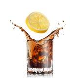 Geïsoleerde plons van kola in glas met citroen stock afbeeldingen