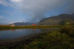 Geïsoleerde tenten in Alpen in regenboog royalty-vrije stock afbeeldingen