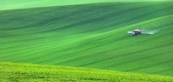 Geïsoleerde tractor op groene gebieden stock fotografie
