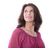 Geïsoleerde vrouw die op middelbare leeftijd in roze blouse zijdelings of aw kijken stock afbeelding