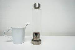 Geïsoleerde witte ceramische kop en handige glasfles royalty-vrije stock afbeelding
